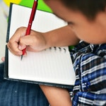 Child writing nature journaling